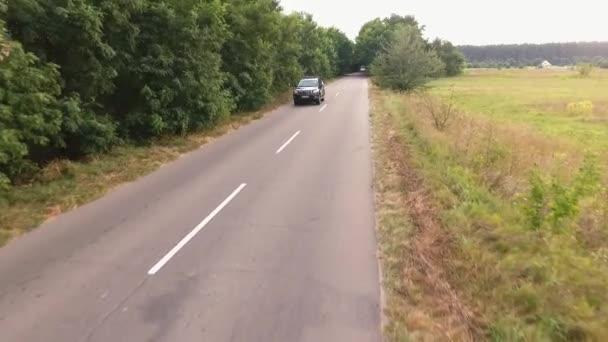 Moderní automobil je na koni venkovské cestě. Lidé cestují autem. Krajina na silnici z města. Fotografování ze vzduchu. Střelba z dron