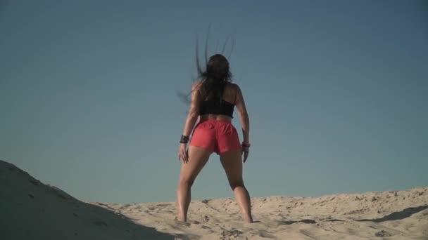 Opálená dívka s krásným tělem tanec twerk na beach Sexy žena pohyby její zadek, stojící na písku krásná žena s atraktivní tělo třese její zadek venku docela mladá dívka tančí