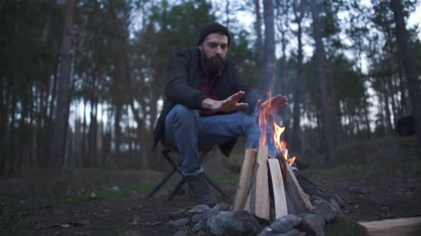 A young bearded guy sitting in the chair and warming up his hands near fire. Forester by the fire in the forest.
