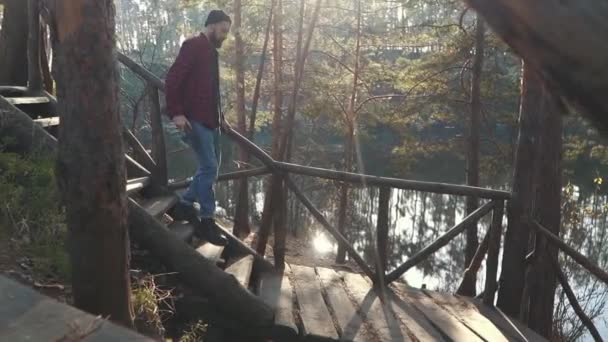 Bearded guy with axe in hands walk by wooden stairs near amazing forest with lake. Young bearded man with an axe outdoors.