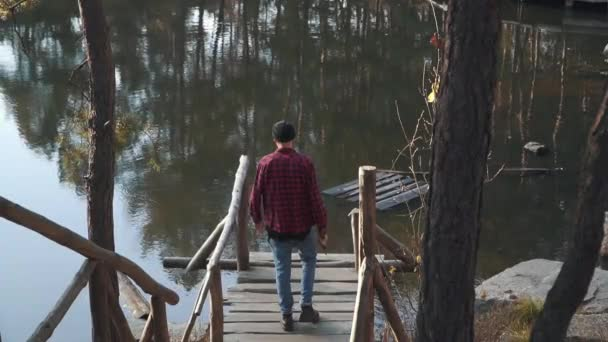 Brutal bearded man walk to a lake by bridge witn an axe in his hand. Young bearded guy with an axe outdoors.