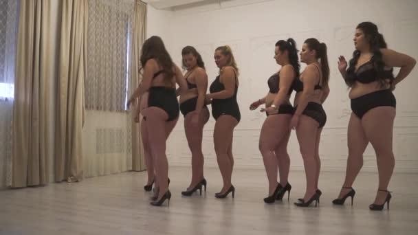 Gruppe von Plus-Size-Models posiert im Studio. Positive Plus-Size-Models in schwarzen Dessous professionelles Make-up und Frisur bleiben in einer Reihe und posieren.