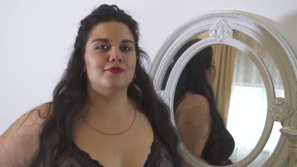 Plus Size Model betrachtet ihr Spiegelbild im Spiegel lächelnd und genießt ihr Aussehen.