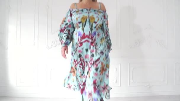 Plusz -méret modell egy szép ruhát, világos stúdió pózol. Kövér nő a szép ruhában pózol.