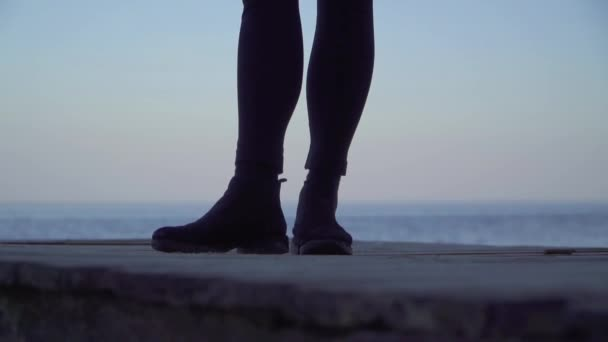 Female legs standing on a wooden platform outdoors. Legs of a woman in tight-fitting leggings and boots against the background of the water surface.