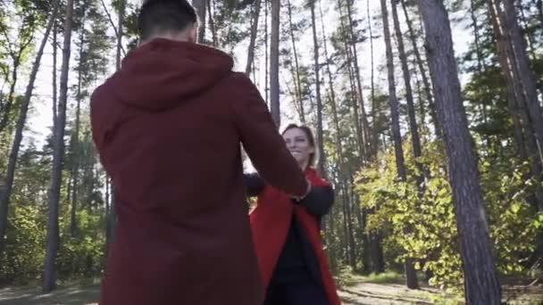 junges Paar, das im Wald vor dem Hintergrund schöner Kiefern tanzt. Ein verliebtes Tanzpaar. der Kerl dreht sich mit seiner Freundin. schöne kaukasische Mädchen tanzen mit ihrem asiatischen