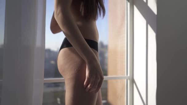 Nahá krásná bruneta s dlouhými vlasy stojí poblíž okna uvnitř domu. Smyslná a vášnivá dívka. Krása ženy s atraktivní tělo v černé kalhotky. Ženský zadek v prádle.