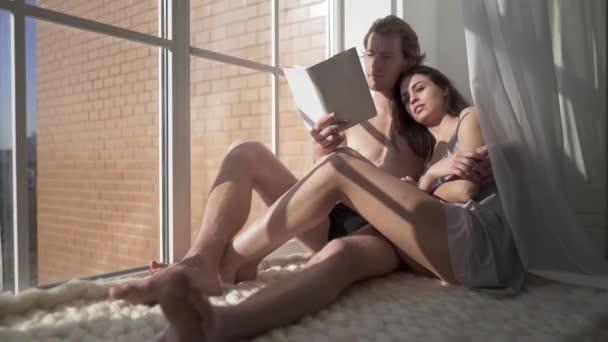 Nacktes paar in Umarmungen lege mich auf Boden und Mensch lesen Sie ein Buch für seine schöne, sinnliche junge Frau. Weiblich ist so glücklich und immer gut gelaunt. Jung und sexy Paar in Liebe Umarmung