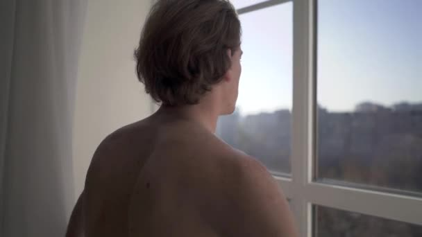 Naked young man stand near window from floor to ceiling and watching amazing city view from high rise building.