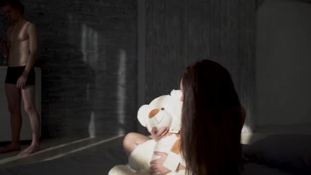 Krásná dívka s tmavými vlasy na prádlo všeobjímající bílý medvídek sedící na posteli. Pěkný nahý chlap stojí vedle postele pomocí svého smartphonu a píše zprávu na mobil