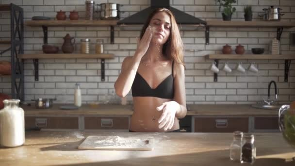 Young sexy hot brunette with long hair in bra put wheat flour at her face and breast in loft kitchen.