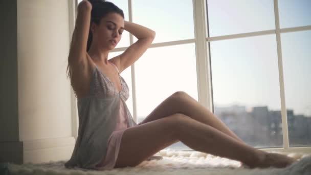 Krásná dívka v noční košili, sedí u okna od podlahy ke stropu. Mladá žena v pyžamu rovnání vlasy dlouhé.