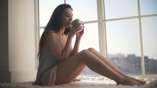 Krásná dívka v noční košili, sedí u okna od podlahy ke stropu. Mladá žena v pyžamu pití ranní kávu a při pohledu z okna.