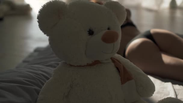 Fiatal nő a fehérnemű az ágyon tökéletes test. Mackó, a háttérben egy meztelen lány feküdt háttal a kamerával. Mackó fókusz lány.