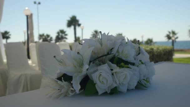 Closeup wedding bouquet of white lilies and white roses decorate tablecloth on the blur sunny resort background