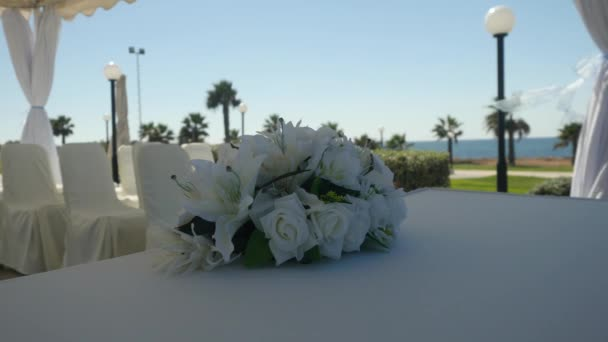 Closeup wedding bouquet of white lilies and white roses decorate tablecloth on the blur sunny resort background outdoors