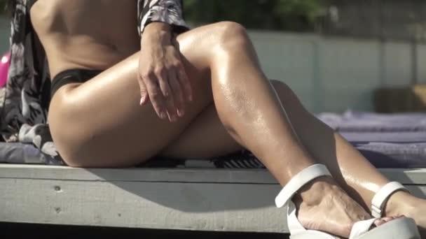 Tökéletes test egy fiatal nő, ezüst úszás ruha, fekvő szolárium és napozás. A gyönyörű hölgy szabadidős