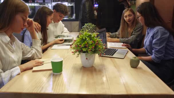 Young people sitting in a cafe at the table reading magazines and books. Students spend time in fast food healthy eating preparing for exams.