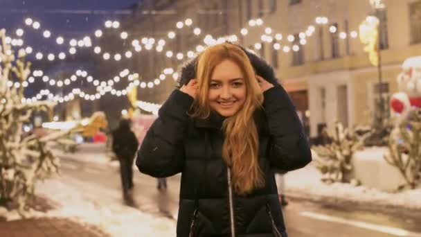 Cheerful woman dances outdoors under snow fall. Happy lady puts hood with fur on her haed and smiles