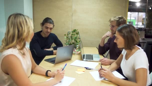Four young entrepreneurs discuss new strategies in start-up using laptops in office meeting room