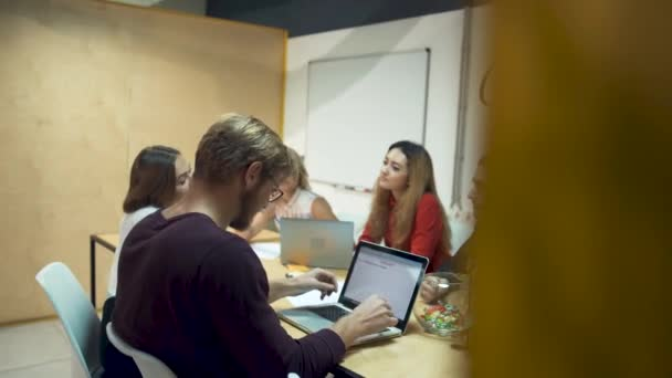 Team of young successful entrepreneurs are working hard on a new startup and discuss new ideas in office meeting room
