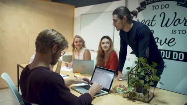 Small team of young successful entrepreneurs working hard on a new startup and discuss new ideas in office meeting room