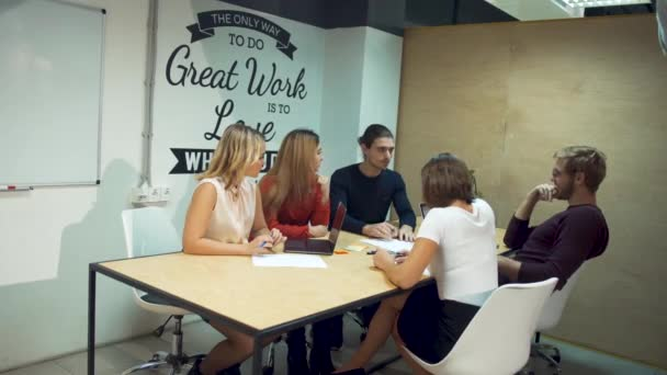 Young entrepreneurs discuss new strategies in start-up using laptops in office meeting room