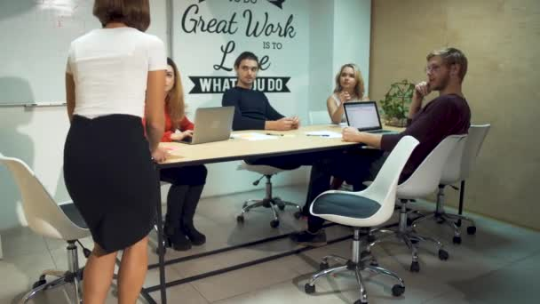 A colleague joins the team of entrepreneurs to discuss a strategy in new startup in office meeting room