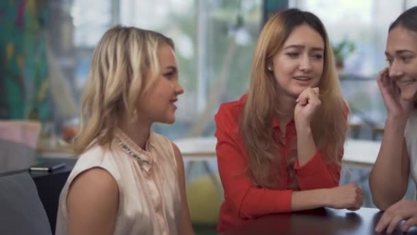 Three cheerful girls sitting at boardroom table during a break in a business meeting.