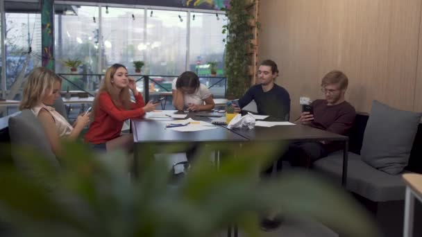 A company of young people sitting at boardroom table on the background of a window overlooking a busy street typing and texting on cell phones.