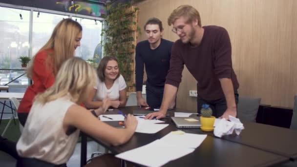 Öt fiatal ember intenzíven a tervek, tárgyaló asztalnál megvitatása. Elemzés napi üzleti tervek.