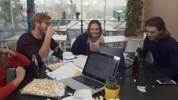 Pět různých kolegové v jásot náladu cinkání sklenic s pepsi zároveň slavit něco v moderní kanceláři