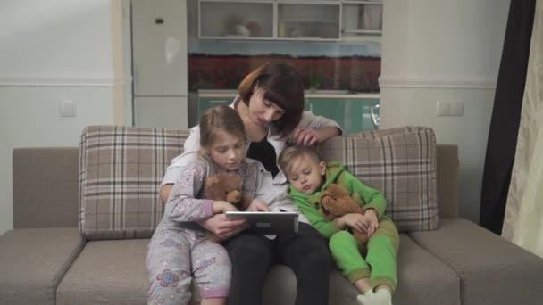 Šťastný matka a dvě děti sedí na pohovce. Žena ukazuje tablet pro děti. Rodinná dovolená.