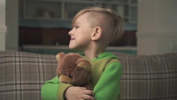 Portréja egy smilling aranyos vidám kisfiú pizsama átölelve egy mackó áll a nappaliban. Boldog vidám gyermek. Lassú mozgás.