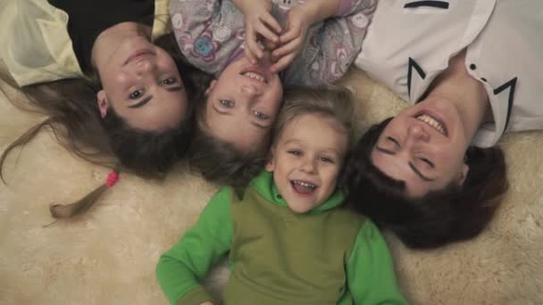 Portrait of happy family of four people laying on fluffy carpet on the floor, smiling. Fun family holiday.