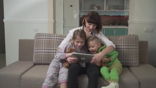 Happy mother and two children sitting on the sofa and look at the tablet. Family holiday.