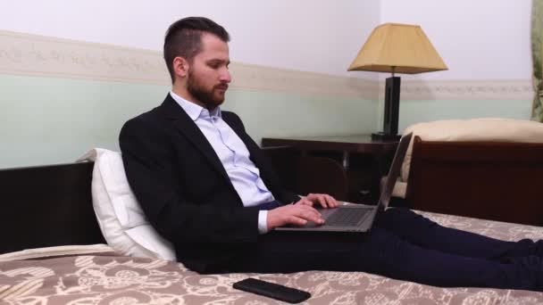 Pohledný podnikatel v obleku sedí s notebookem v posteli. Pohledný vousatý muž pracuje v ložnici.