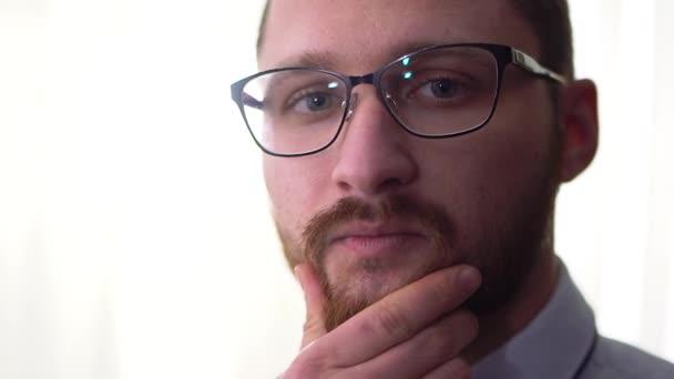 Portréja egy töprengő szép szakállas üzletember szemüveg elszigetelt fehér háttér közelről.
