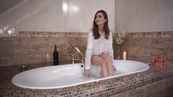 Mladá žena sedí na okraji vany, hrát si s pěnou. Láhev vína a svíčky jsou blízko. Roztomilá dívka se těší v koupelně.