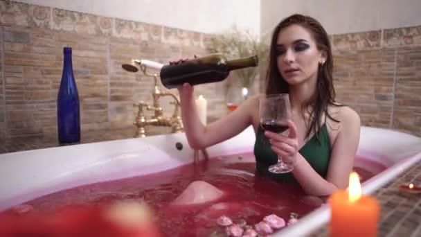 Krásná žena nalévá červené víno sklo ale valí do vody ve vaně s růží