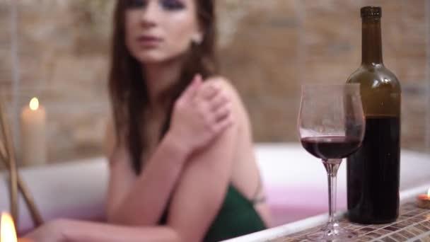 Eine Flasche Rotwein mit Glas befindet sich im Badewannen-Rand. Lächelnde Frau im Hintergrund sitzt in Badewanne