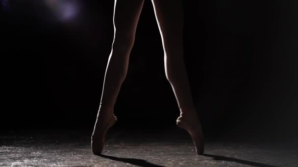 Slow motion shot of ballerina dancing in spotlight on black background in studio. Ballet dancer shows classic ballet pas wearing tutu and pointe shoes.