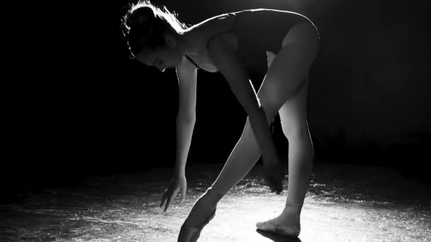 Cute flexible ballerina standing on her pointe ballet shoes in spotlight on black background in studio. Black and white shot. Slow motion.
