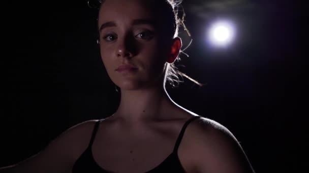 Portrait professional young ballet dancer standing in spotlight on black background in studio. Ballerina shows classic ballet pas. Slow motion.
