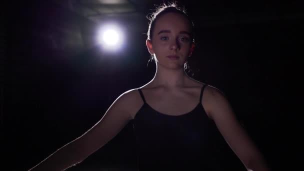 Portrait professional cute ballet dancer standing in spotlight on black background in studio. Ballerina shows classic ballet pas. Slow motion.