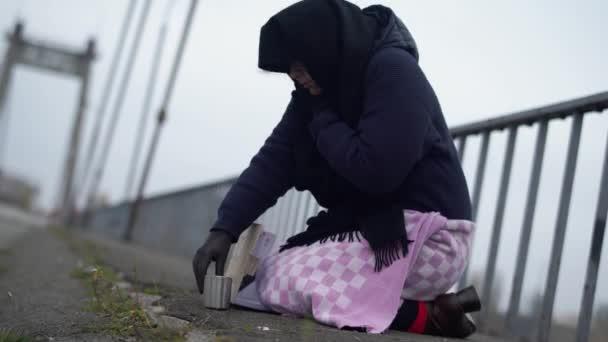 erwachsene obdachlose Frau sitzt bei kaltem, windigem grauen Wetter auf der Brücke und bittet um Almosen und Hilfe und trinkt etwas aus Tasse