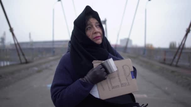Porträt einer erwachsenen traurigen Obdachlosen, die bei windigem, grauen Wetter auf der Brücke ausharrt und um Almosen und Hilfe bittet