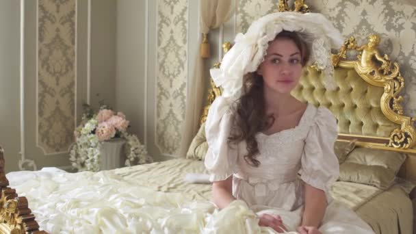 Young beautiful woman in white vintage ball dress and hat siting on the huge golden bed and hiden with mobile phone