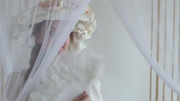 perfekte junge Frau mit Seidenhut und Blumen fächert ihr Gesicht mit weißem Federfächer, der sich in Großaufnahme hinter Schleier versteckt. Serie echter Menschen auf weißem Hintergrund.