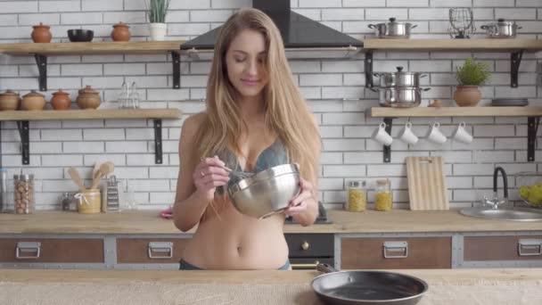 Mladá žena v prádle kypřícího rozšleháme ve velké mísy stojící v kuchyni